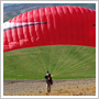 A red paraglider about to launch